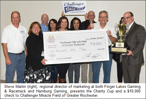 Steve Martin (right), regional director of marketing at both Finger Lakes Gaming & Racetrack and Hamburg Gaming, presents the Charity Cup and a $10,000 check to Challenger Miracle Field of Greater Rochester.